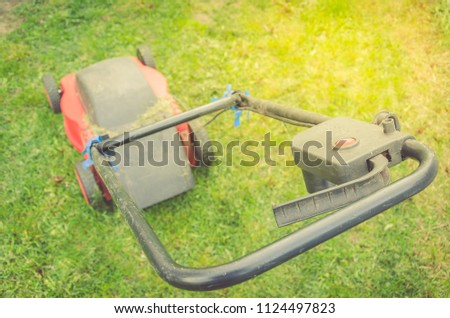 red lawn mower on a green lawn/red lawn mower on a green lawn. Top view #1124497823