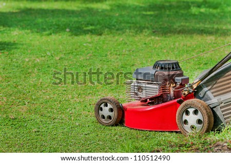 Red lawn mower on green grass in sunny day