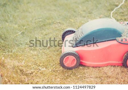 red lawn mower on the lawn/red lawn mower on the green lawn. Copyspace. Toned #1124497829
