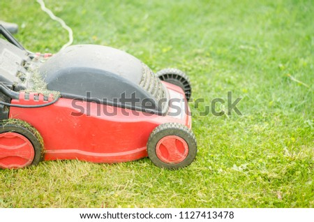 red lawn mower on the lawn/red lawn mower on the green lawn. Selective focus #1127413478