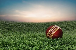 Red Leather Cricket Sport Ball on grass with sky