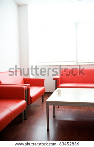 Red leather sofa and white table at waiting room.
