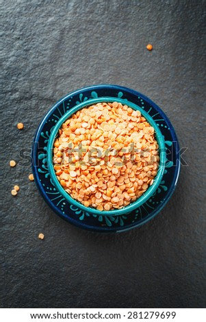 Red Lentil Halves in Authentic Turkish Dishware on Black Stone Background. Top View.