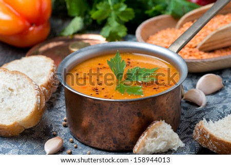 red lentil soup with pepper and spices in a copper saucepan, horizontal, close-up