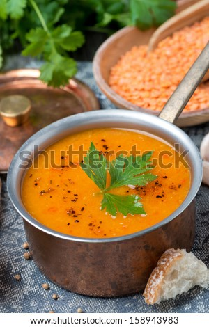 red lentil soup with pepper and spices in a copper saucepan, vertical, close-up