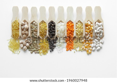 Red lentils, green lentils, beans, chickpeas, bulgur, unexploded corn, vermicelli, black pepper, couscous pasta, rice, wooden legumes in spoons and on a white background Stock photo ©