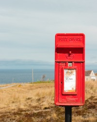 Red letterbox by the sea along the north coast 500