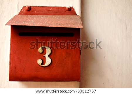Red letterbox on cream wall, number 3.