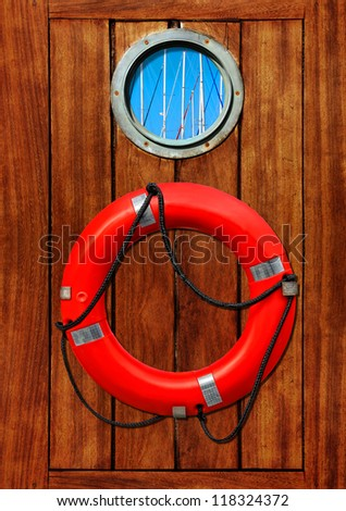 Red life buoy and porthole on a wooden wall