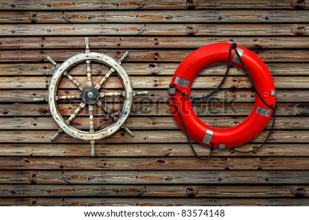 Red life buoy and steering wheel of the ship on a wooden wall