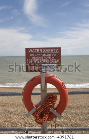 Red Lifebuoy and warning sign on the beach at Hythe, in Kent