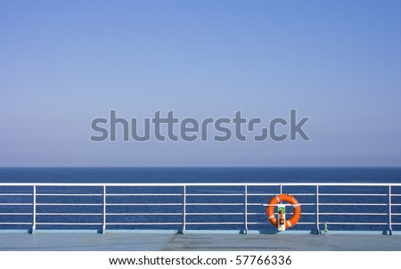 Red Lifebuoy in front of the blue sea and the white ship