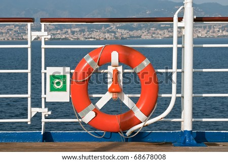 Red Lifebuoy in front of the blue sea on a cruise ship