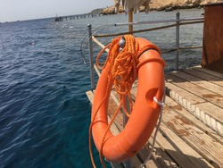 Red lifebuoy with rope on a wooden pier near sea