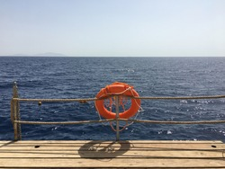 Red lifebuoy with rope on a wooden pier near sea, outdoor. Lifebuoy at the pier. Save lifebuoy and blue water.