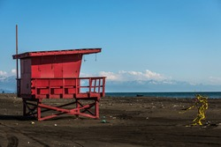 Red lifeguard rescue tower on the beach with blue sky background, Sea lifeguard tower. Desolate seascape.