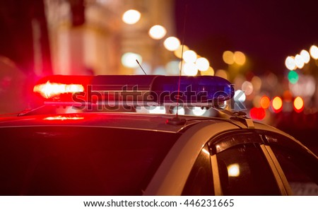 Red light flasher atop of a police car. City lights on the background.
