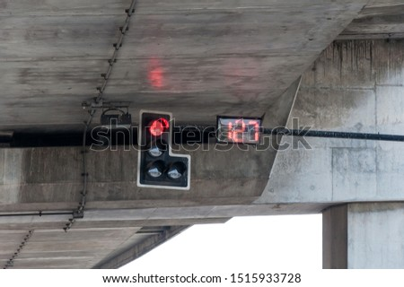 Red light from the signal pole with the digital countdown number in the intersection under the expressway bridge.