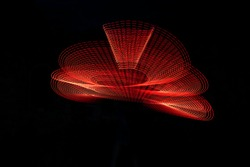 Red Light Painting, long exposure photography, loop and swirl against a black background