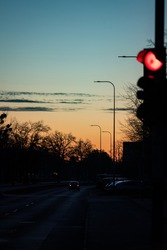 Red light signal with the city silhouette in the morning sunlight. Dark, morning sunrise at the city. Urban landscape photography.