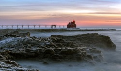 Red Lighthouse in Door County Wisconsin along Lake Michigan on a cold winter morning during sunrise