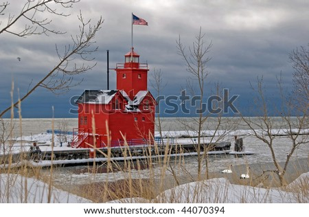 red lighthouse in winter with swans