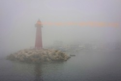 Red lighthouse near the shore, dark water around. Everything is in thick fog. In the distance the outlines of a sea village. Bad visibility.