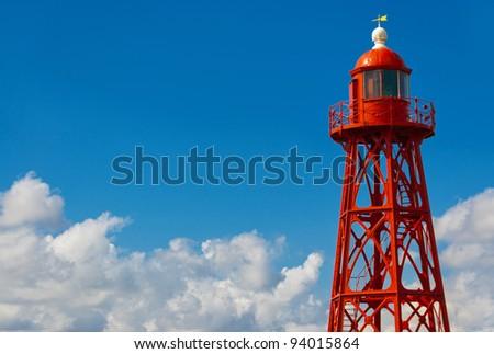 Red lighthouse on blue sky background