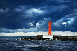 Red lighthouse with a solar battery against dark sky. Dramatic sky, waves, water splashes, storm. Baltic sea. Nature, weather, climate, alternative energy, power in nature, safety. Symbol of hope