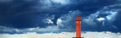 Red lighthouse with a solar battery. Dramatic blue sky, dark storm clouds. Baltic sea. Nature, weather, climate, alternative energy, power in nature, safety. Symbol of hope and peace
