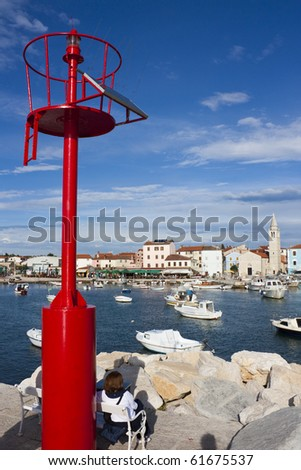 Red lighthouse with solar panel and woman sitting on bench in harbor of Fazana in Croatia