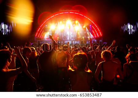 Red lights of excitement cover the crowd of dancing people #653853487