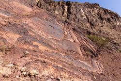 Red limestone and dolomite rock formations in Hajar Mountains on Arabian Peninsula, United Arab Emirates, Hatta.
