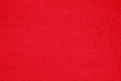 Red linen fabric rough texture. Christmas canvas for textiles, clothing, interior, creativity in Scandinavia, Provence, rustic style. Hard texture, knots are visible. Monochrome vinous background.