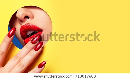 Red lips peep through the hole in the yellow paper. Fingers at the mouth with bright red manicure.Lipstick, cosmetics, makeup, nail polish, beautiful fingers, fashion, beauty.