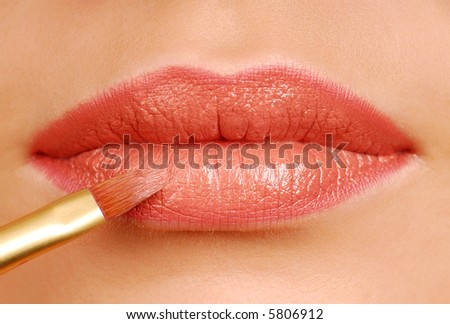 Red lipstick cosmetic brush. Make-up tool. Woman lips close-up.