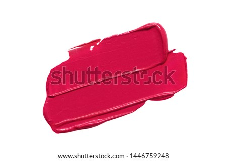 Red lipstick smear smudge swatch isolated on white background. Cream makeup texture. Bright color cosmetic product stroke swipe sample