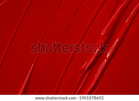 Red lipstick smudged background. Lipstick or other makeup product swatch. Acrylic paint smeared texture. Red gouache brush painted wallpaper. Can be used as an advertisement banner, text background.