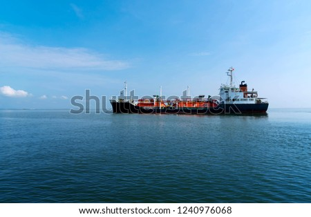 Red Liquefied Petroleum Gas LPG tanker in the sea out of the port in gulf of Thailand. Cargo ship against blue ocean.