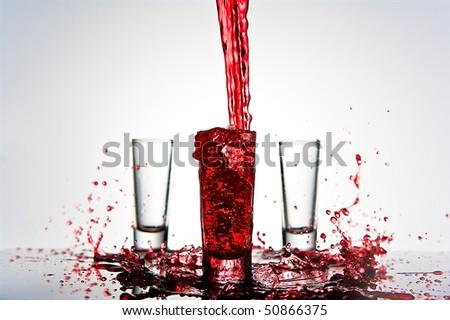red liquid splashes into shot glass