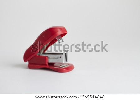 Red little stapler on white background