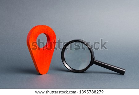 Red location pointer and a Magnifying glass on a gray background. Concept of navigation and venue. Tourism and travel. Spying on the citizens.. Orientation around the city, location of events #1395788279