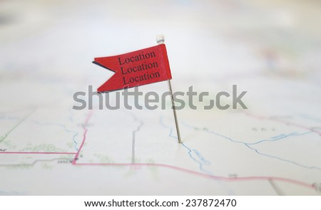 Red locator flag on a map with Location Location Location text                               #237872470