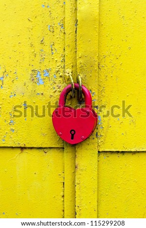 Red lock on a rusty yellow door