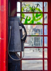 Red London phone box in Soho London. Dilapidated and graffiti covered.