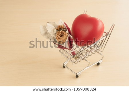Red love heart and dried flower bouquet in shopping cart on wood table #1059008324