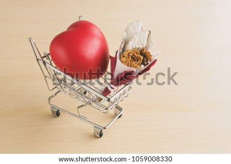 Red love heart and dried flower bouquet in shopping cart on wood table #1059008330