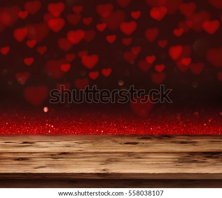 Red love heart in a dark background in front of a empty wooden table for a valentines day concept #558038107