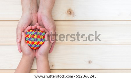 Red love heart in puzzle jigsaw pattern on son child kid's hand supported by mother's parent caregiver person on white wood background, symbolic health care campaign for World Autism Awareness day