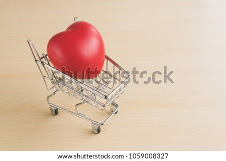 Red love heart in shopping cart on wood table #1059008327